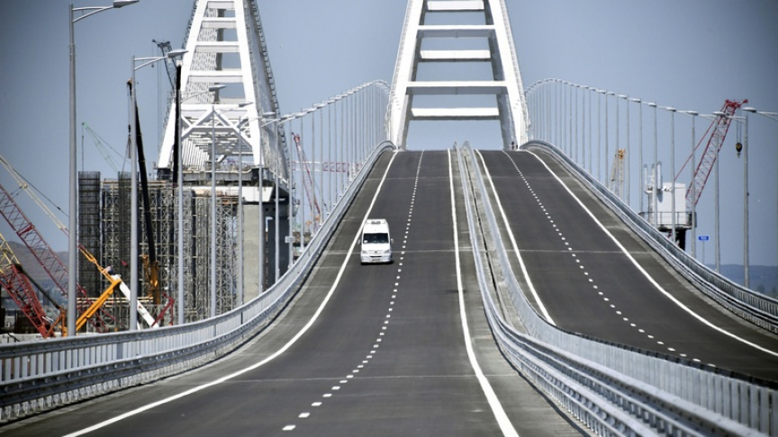 A vehicle drives along a bridge, which was constructed to connect the Russian mainland with the Crimean Peninsula across the Kerch Strait