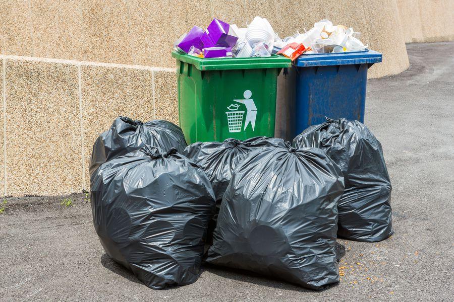 Close up Trash bin and black garbage bag in sunny light